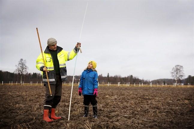 Christer Finne mäter tjälen en gång i månaden och rapporterar värdet till Miljöcentralen. Statistiken används för att göra översvämningsprognoser och konstruktionsberäkningar. Barnbarnet Ines Tuohimaa gör honom sällskap.