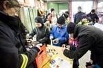 Musse Asplund, Sky Linman, Sara-Li Asplund (skymd) och Kim Asplund sorterar batterier i brandbilsgaraget.