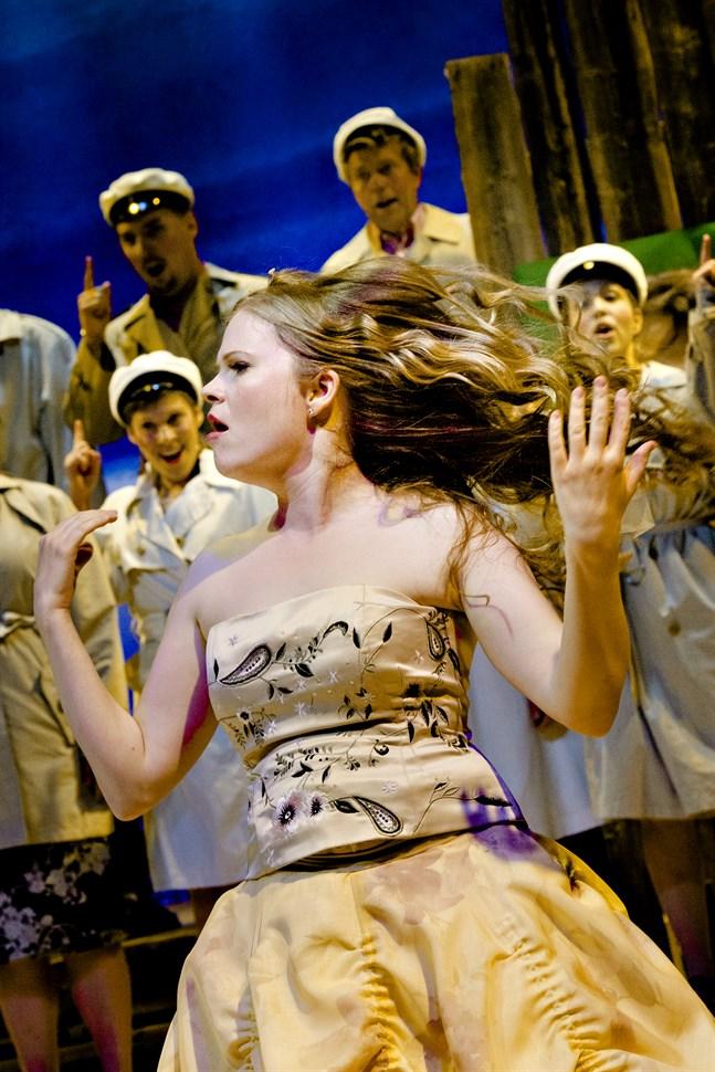 Annami Hylkilä som hormonstinn jungfru tillsammans med kören Kokkola Opera Harrbådavoices Ensemble.