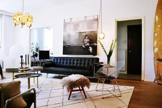 I vardagsrummet hänger Elinas favorittavla och Tuukkas surfbräda från Kalifornien. Stolen kommer från Bertoia.