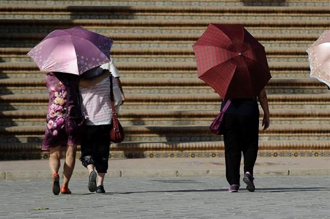 Det är i dag också bekräftat att värmeböljorna i Europa 2018 och 2019 enbart kan förklaras om man inkluderar den globala uppvärmningen.  På bilden ett par turister som tar paraply till hjälp för att skydda sig mot solen och temperaturer på 45 grader celsius i Spanien.