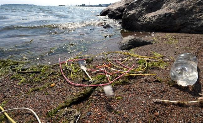 Plastskräp, stubintråd och en plastflaska på strandkanten.