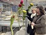 Människor sätter fast gula och röda rosor i stängslet vid attentatsplatsen i Stockholm.