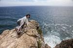 Ciceronen Rocío Martínez Moya tar det försiktigt – det är mer än hundra meter ned till havet från klippkanten.
