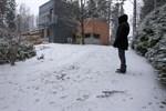 Åsa Eriksson i Gerby visar spåren (närmast i bilden) av vargen som korsade hennes och grannes gårdsplan på onsdagen.