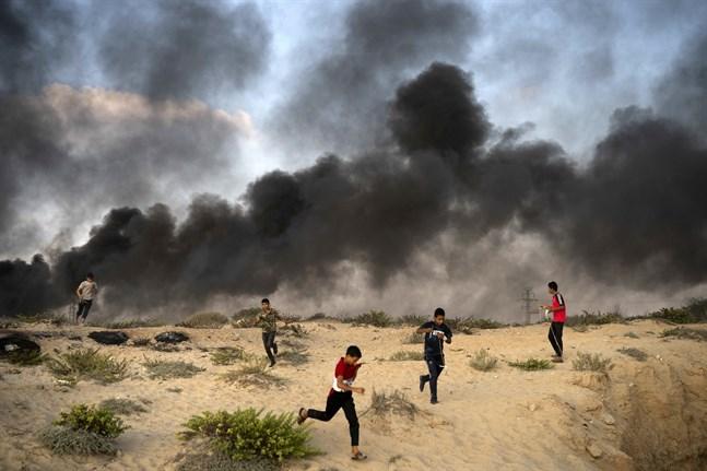 Unga palestinier springer från en protest i närheten av gränsen tidigare i veckan för att undvika tårgas. Vissa av demonstranterna har bränt bildäck vid gränsen för att undvika upptäckt. Arkivbild.