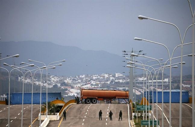 Containrar och lastbilar över en bro på gränsen mellan Colombia och Venezuela hindrar sedan i onsdags hjälpsändningar in i det krisdrabbade landet.