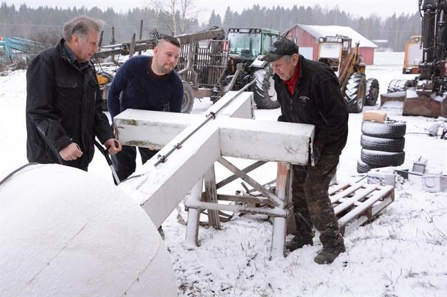 Per-Erik, Daniel och Lars-Åke Hannus tog ner det gamla korset från klockstapeln i Sideby och sedan dess har det förvarats på Näveråsen i Närpes. Nu ska korset förstöras. Bilden från december 2018.