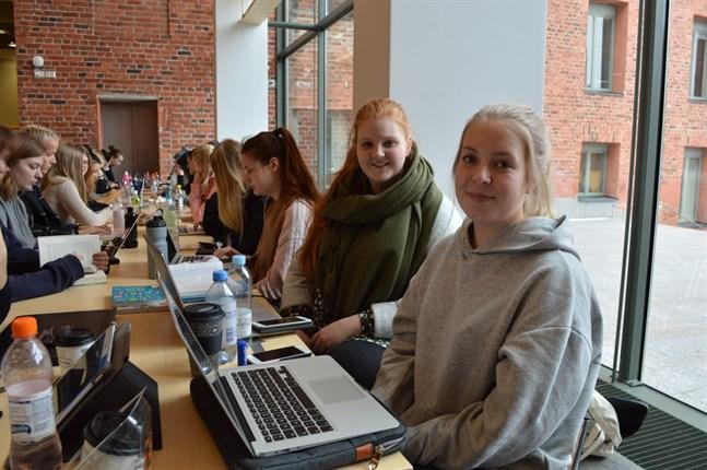 Sophie Jakobsson (till höger) och Amanda Björk passar på att studera medan de köar.
