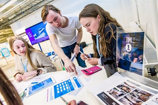 Frans Villanen från Företagsbyn förklarar spelets regler för Sofia Prest och Anna Sandström i Team 1.