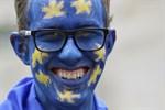 En demonstrant med ansiktet målat som EU-flaggan.