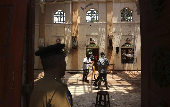 En polis står vakt när överlevare arbetar i kyrkan S:t Sebastian norr om huvudstaden Colombo.