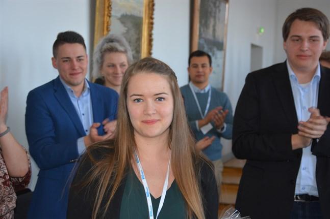Tidigare ordförande Christoffer Ingo och återvalde vice ordförande i Svensk ungdom, Nicholas Kujala till höger applåderar nye förbundsordförande Frida Sigfrids som valdes vid kongressen i Kristinestad på söndagseftermiddagen.