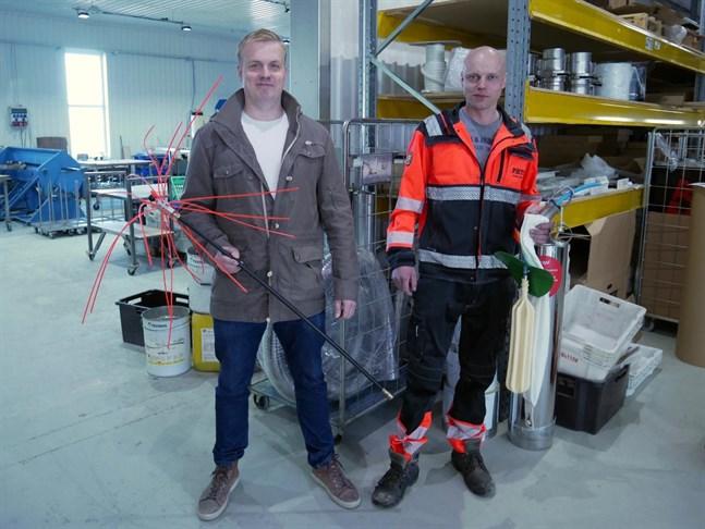 Kristian Lindfors till vänster håller i en skorstensputsare som används innan man kan renovera den. Toni Hakala till höger håller i en ballong som används vid gjutning av skorstenar.