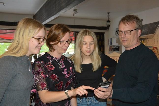 Mikaela Björklund kollar vad intressant hennes svåger Staffan Holmberg har noterat i resultatflödet. Björklunds döttrar Paola (till vänster) och Julia har även deltagit i valkampanjen, Paola har hjälpt till med Instagramkontot och Julia ansvarat för den grafiska utformningen av reklamen.