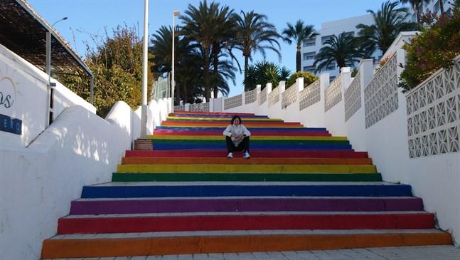 Här sitter Debbie på en regnbågsrandig trappa i Nerja i Spanien.