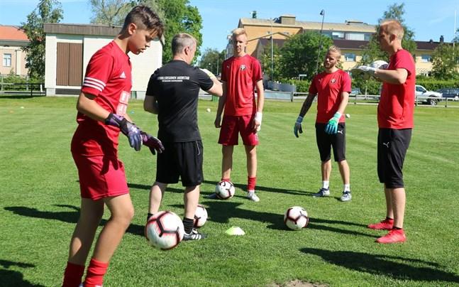 Mikael Johnson med ryggen mot kameran instruerar sina målvaktstränare Hannes Käldström, Emil Öhberg och Topi Valtonen (till höger) under ett fotbollsläger 2019. Till vänster syns Wilhelm Söderman.