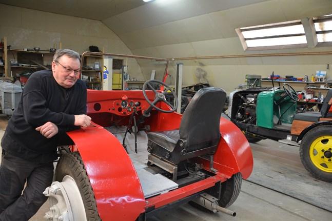 Kurt Nygårds har både en röd och en grön skapelse. Vindrutan ska ännu på plats i biltraktorn av märket International. Sitsen kommer från en butiksbil som tagits ur bruk.