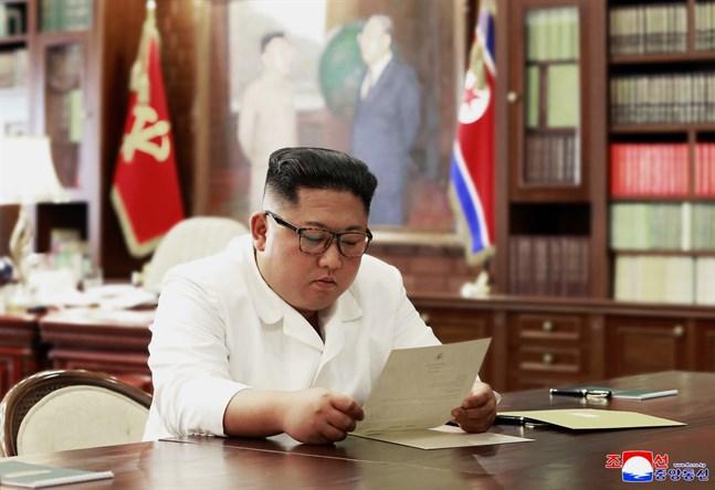 Kim Jong-Un läser brevet som påstås ha skrivits av USA:s president Donald Trump. Bilden kommer från Nordkoreas statliga nyhetsbyrå.