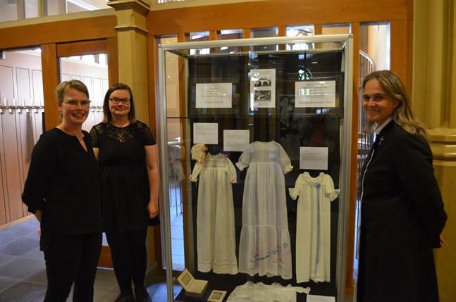 Johanna Backholm, Piritta Pitkämäki Ihatsu som är ungdomsarbetsledare i Vasa svenska församling och Vasa finska församlings pastor Terhi Nissilä framför utställningens äldsta dopklänning.