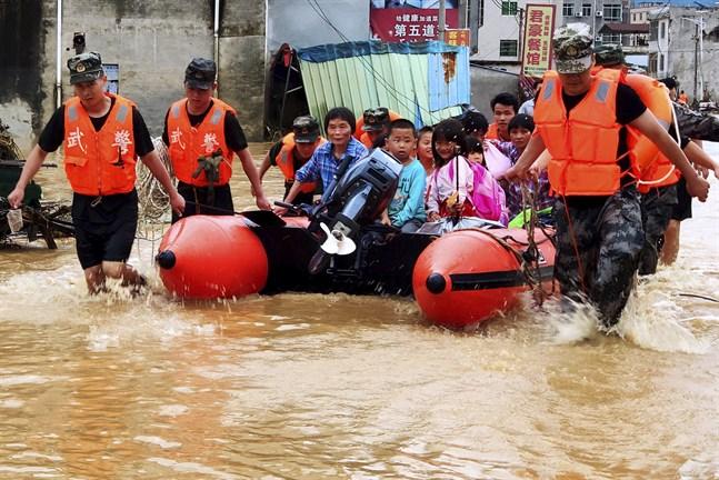 Kinesisk paramilitär polis evakuerar människor efter översvämningar i Heyuan i södra Kina 10 juni 2019. Arkivbild.