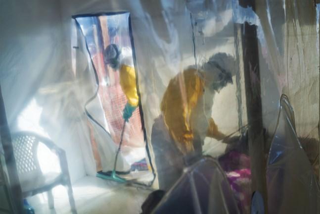 Hälsoarbetare i skyddskläder tillsammans med en isolerad ebolasmittad person i Beni i Kongo-Kinshasa, 13 juli 2019.