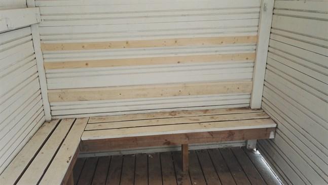 Med hjälp av tre brädor har sprickorna och hålet täckts för. Brädorna är uppspikade på väggen i flickornas omklädningsrum.