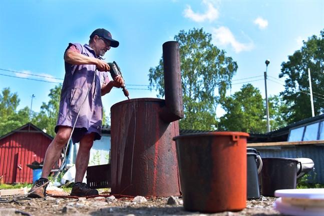 Björn Pettersson som rör om i grytan fylld av rödmylla färg.
