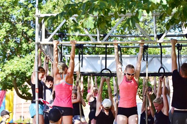 Uthålliga deltagare testar sin styrka på monkey bar hindret.