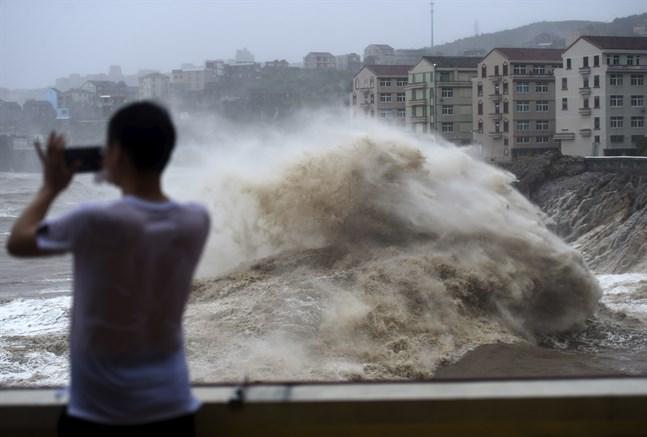 En man filmar när tyfonen Lekima drar in över den kinesiska staden Wenling med flera meter höga vågor.