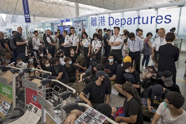 Flygplatspersonal vaktar bakom demonstranter vid avgångshallen på Hongkongs internationella flygplats.