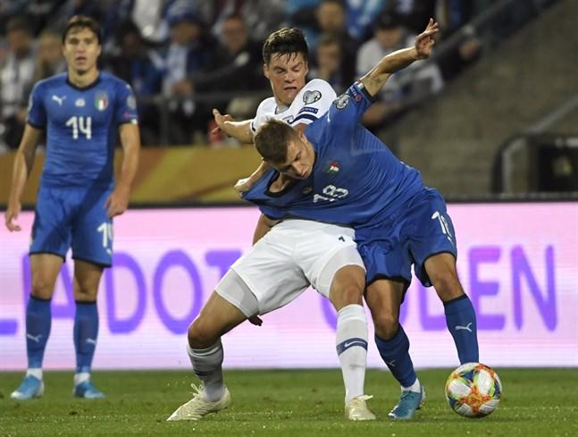 Sauli Väisänen är inte nöjd med domslutet som ledde fram till Italiens straff. Här kämpar mittbacken om bollen med mittfältaren Nicolo Barella.