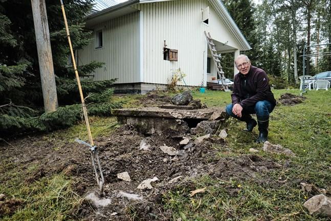 Bengt Lillsjö vid gropen som blixten grävde ner i marken. Bakom honom syns fåran i gräsmattan som blixten rev upp.