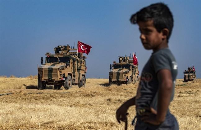 En syrisk pojke ser på då en turkisk militärkolonn kommer in i kurdernas område i norra Syrien.