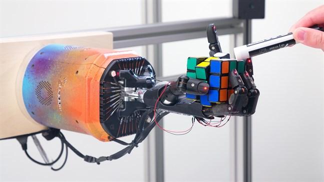 Robothanden klarar av att lösa kuben även när forskarna petar på den med en penna.
