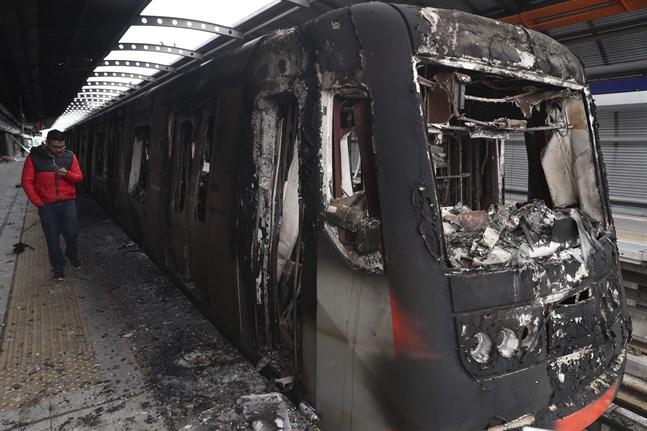 Flera bränder har anlagts i samband med protesterna i Santiago. Här är en tunnelbanevagn som bränts.
