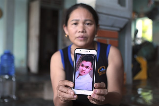 Hoang Thi Ai visar en bild på sin son som befaras vara en av de personer som hittades död i lastbilen utanför London. Migranter betalar flyktingsmugglare upp till en halv miljon kronor för att ta sig från Vietnam till Storbritannien.