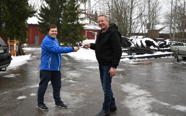 Varsågod, här är telefonen. Leif Erikson (till höger) ger över ett viktigt arbetsverktyg till sin efterträdare Sebastian Strandberg. som är ny vd för Närpes centralantenn.