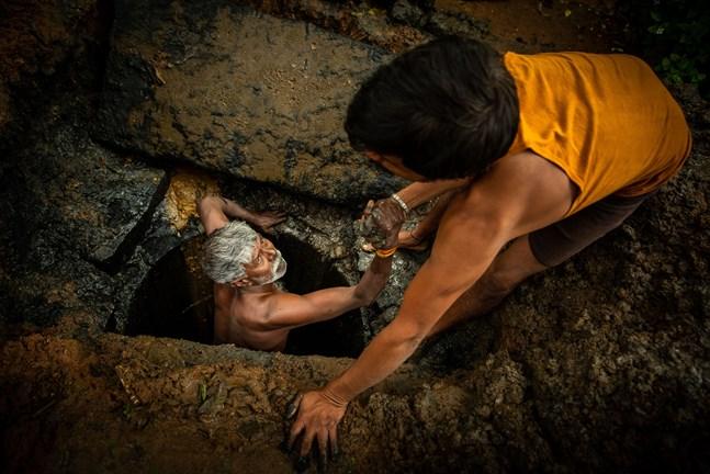 54-årige Kaverappa från Bangalore, Indien, hjälps upp ur latrinhålet han håller på att tömma av en kollega. Kaverappa har arbetat som latrintömmare i 35 år.