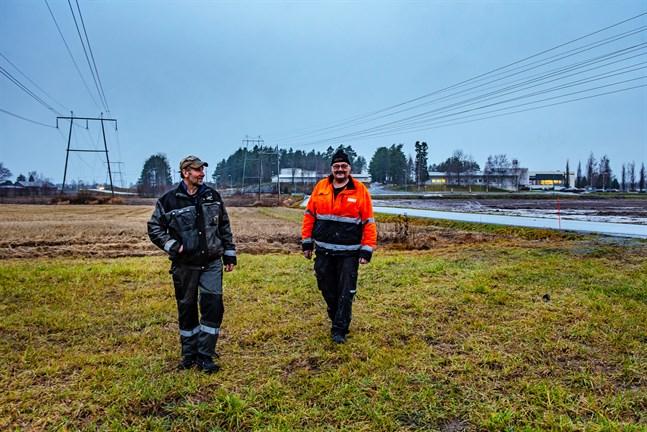 Peter Nyman och Mikael Nynäs står på Nynäs markplätt. Bakom dem ligger den så kallade Stens tomt och på andra sidan vägen är Nymans potatisåker. Här kunde det gott stå en skola, tycker de.