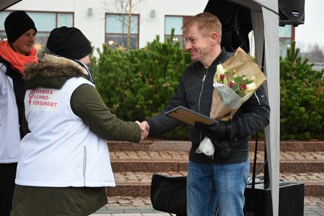 Jennie Wilson och Linda Pellfolk från Svenska kvinnoförbundet i Närpes uppvaktade årets Närpesbo – Arthuras Pilauskas – på julöppningen.