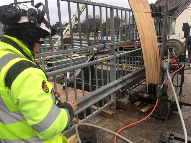 En jobbare manövrerar sågen med en smalt rep av diamanter som bit för bit skär sönder betongväggen i den övre öppningen, som beräknas vara klar nästa vecka.