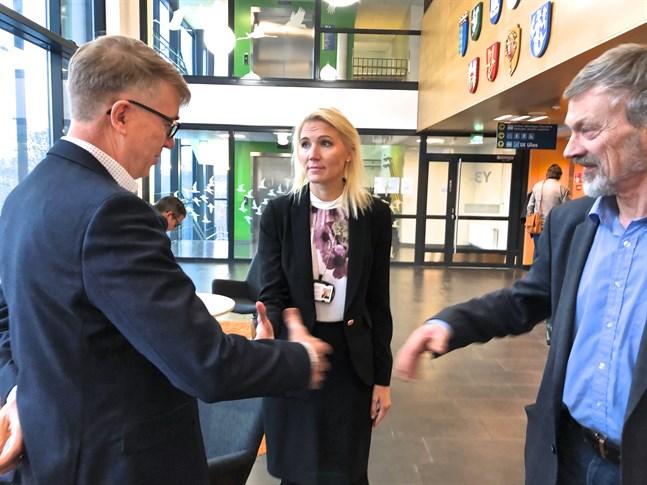 Klartecken för labbaffär. Ari Miettinen, vd på Fimlab, skakar hand med Marina Kinnunen och Michael Luther efter att fullmäktigemötet gett grönt ljus för affären.