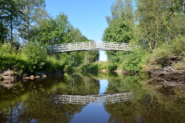 Den här gång- och cykelbron går över ån i Pörtom vid Mattuschvägen, nära den gamla begravningsplatsen. Den nya hängbron skulle gå över ån nära den nuvarande begravningsplatsen längre söderut.