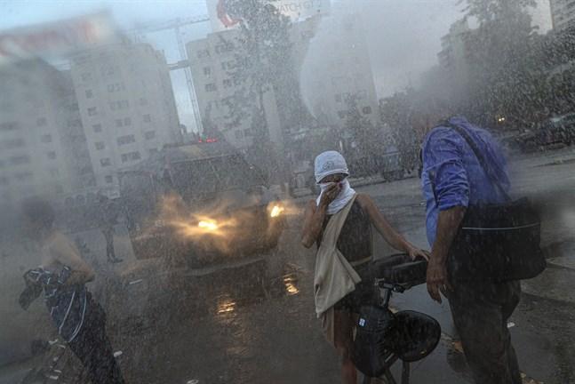 Polisen sprutar vatten på regeringskritiska demonstranter i Chiles huvudstad Santiago.