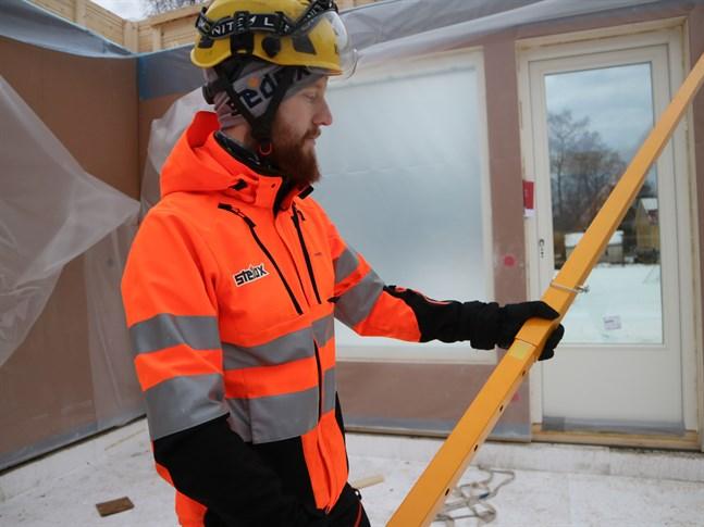 Jimmy Sundström visar upp stödet för träelement. Det fungerar som en vantskruv på en segelbåt. Genom att skruva på stödet kan justera elementet tills det står rakt.