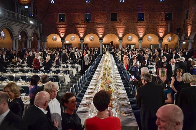 Gästerna sätter sig till bords inför Nobelbanketten i Blå hallen i Stadshuset i Stockholm.