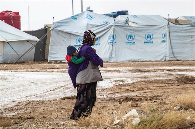 Kvinna bär ett spädbarn i al-Hol-lägret i nordöstra Syrien. På marken syns lite snö. Bilden är tagen den nionde december.