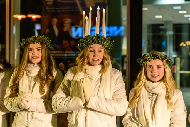 Lucia Marie Brunell med tärnorna Emma Vikman och Alma Långbacka när de sjöng utanför biblioteket i Karleby under luciakvällen i fjol.