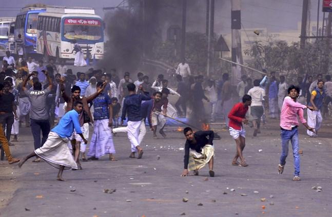 Demonstranter i utkanten av den indiska storstaden Calcutta i Västbengalen kastar sten mot polisen på lördagen.